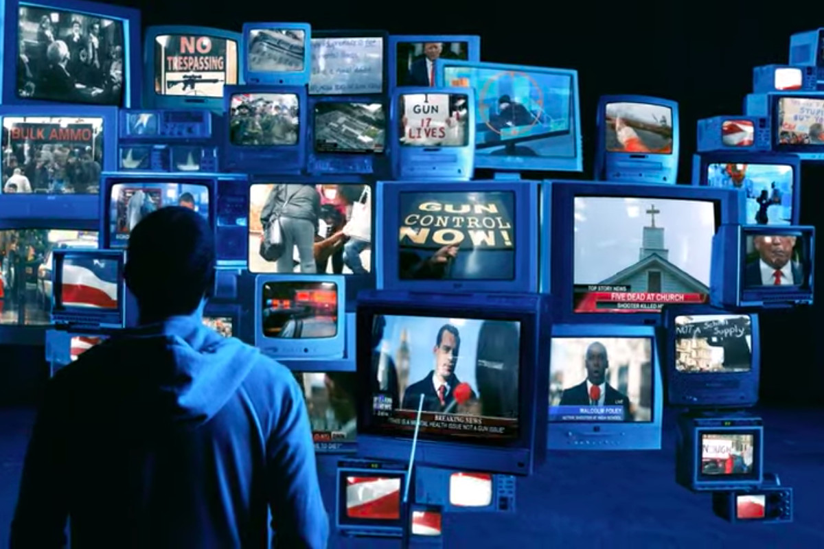 Eminem watches a panoply of screens showing footage of mass shootings. The screens combine to form a map of the United States.