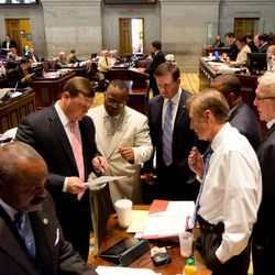 Lawmakers gather at a desk in the House chamber in Nashville, Tenn., to discuss a bill on Friday, April 27, 2012. From left are Reps. G. A. Hardaway, Vance Dennis, Antonio Parkinson, Barrett Rich, Curry Todd and Mike Tuner.