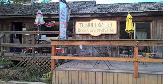 The exterior of a bookstore in Montana. The store's facade is made with weathered wood, and there is a deck that leads to the entrance.