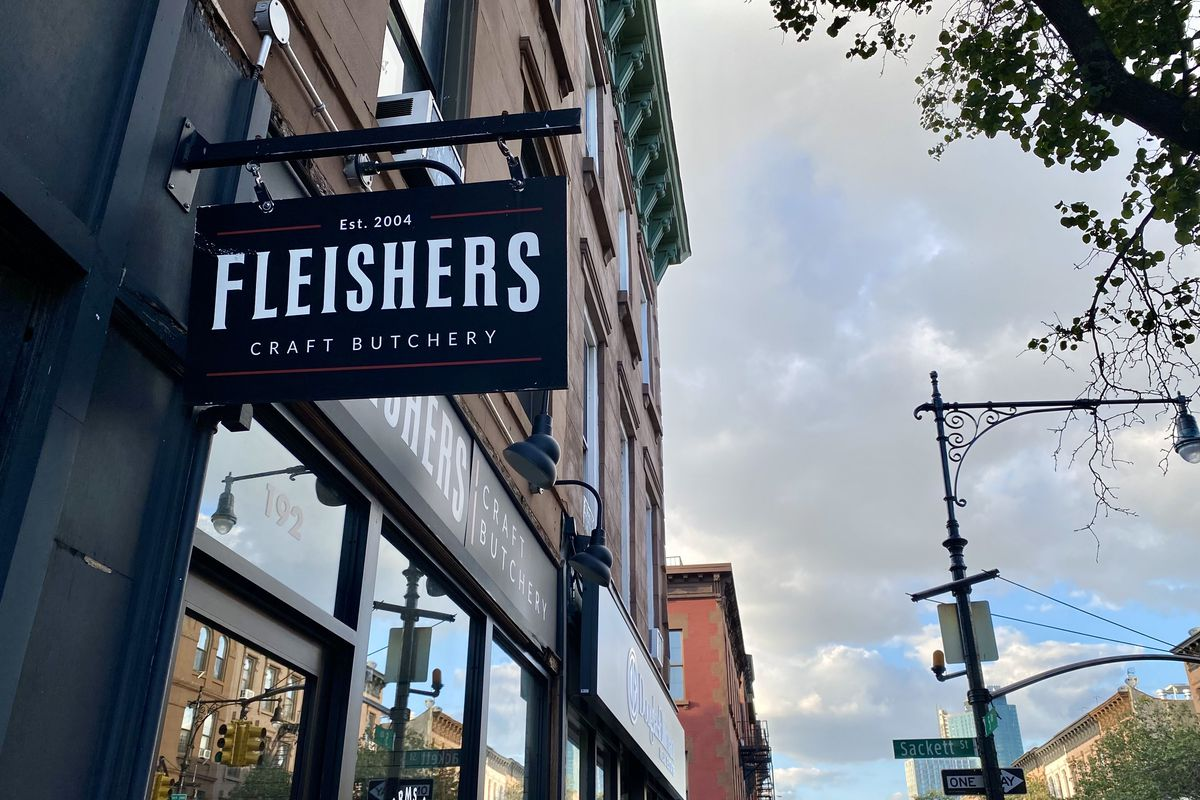"""A black sign with the words """"Fleishers Craft Butchery"""" hangs in a city street. In the background a storefront and clouds in the sky are visible."""
