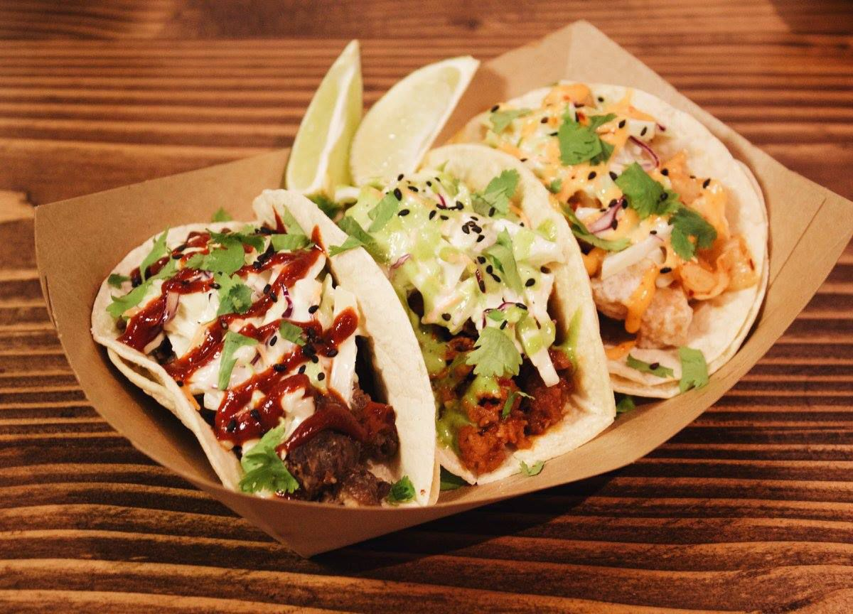 Three Korean fusion tacos sit in a paper container on a wooden counter