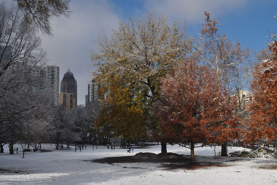 A park dusted in snow with tall buildings behind it.