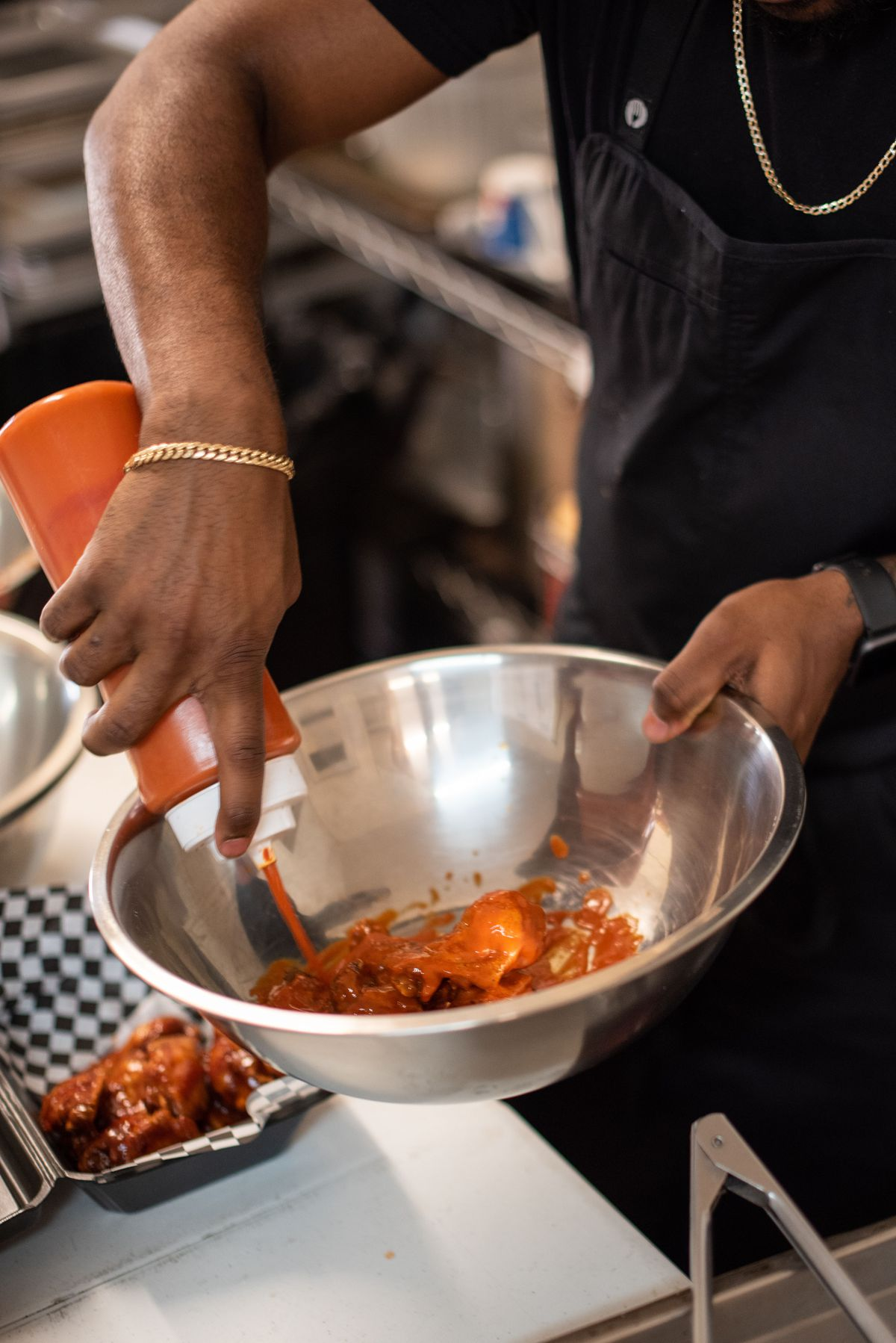 Loading up a shiny metal bowl with sauce for wings.