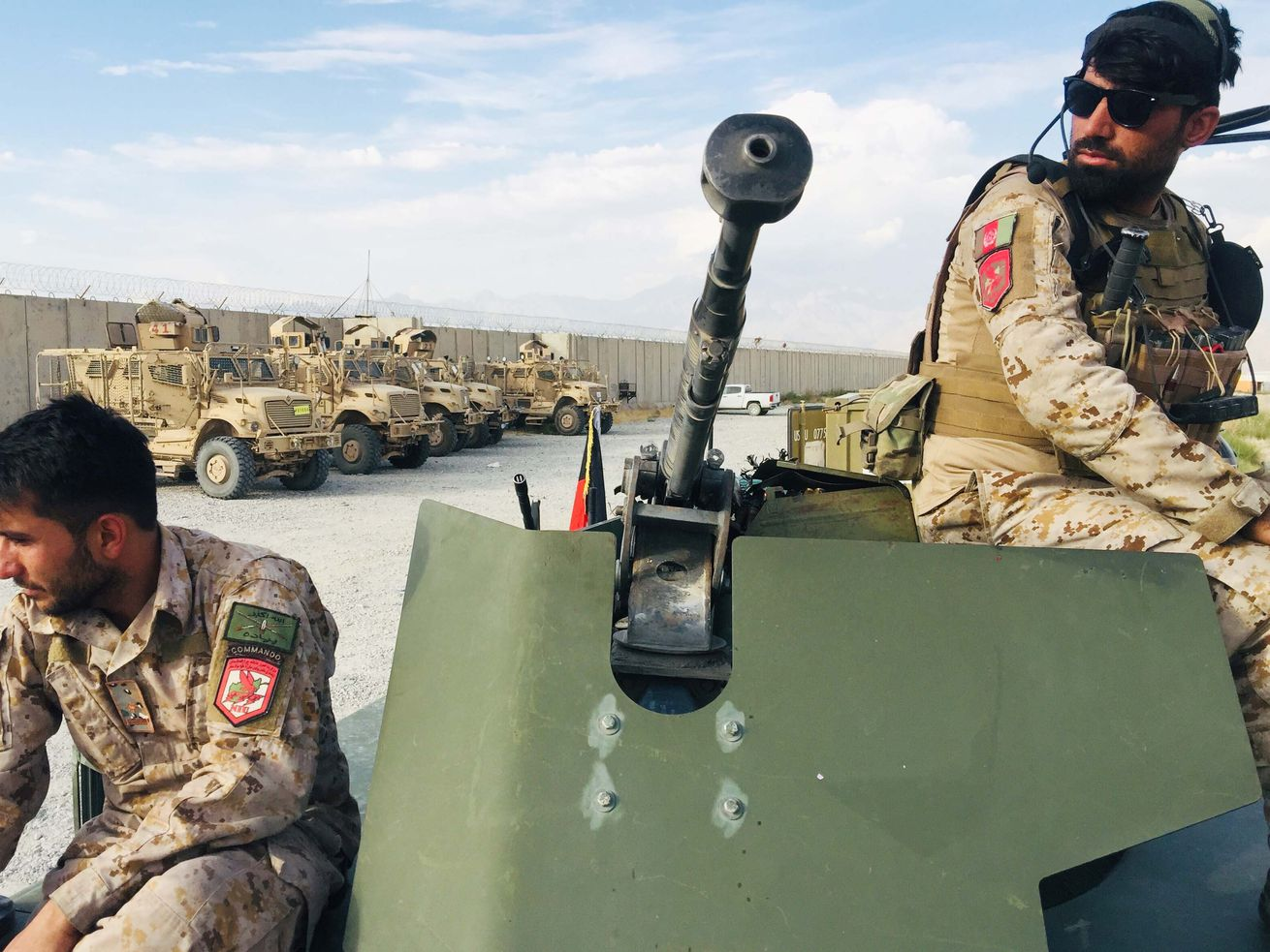 Two soldiers sit on an armored vehicle.