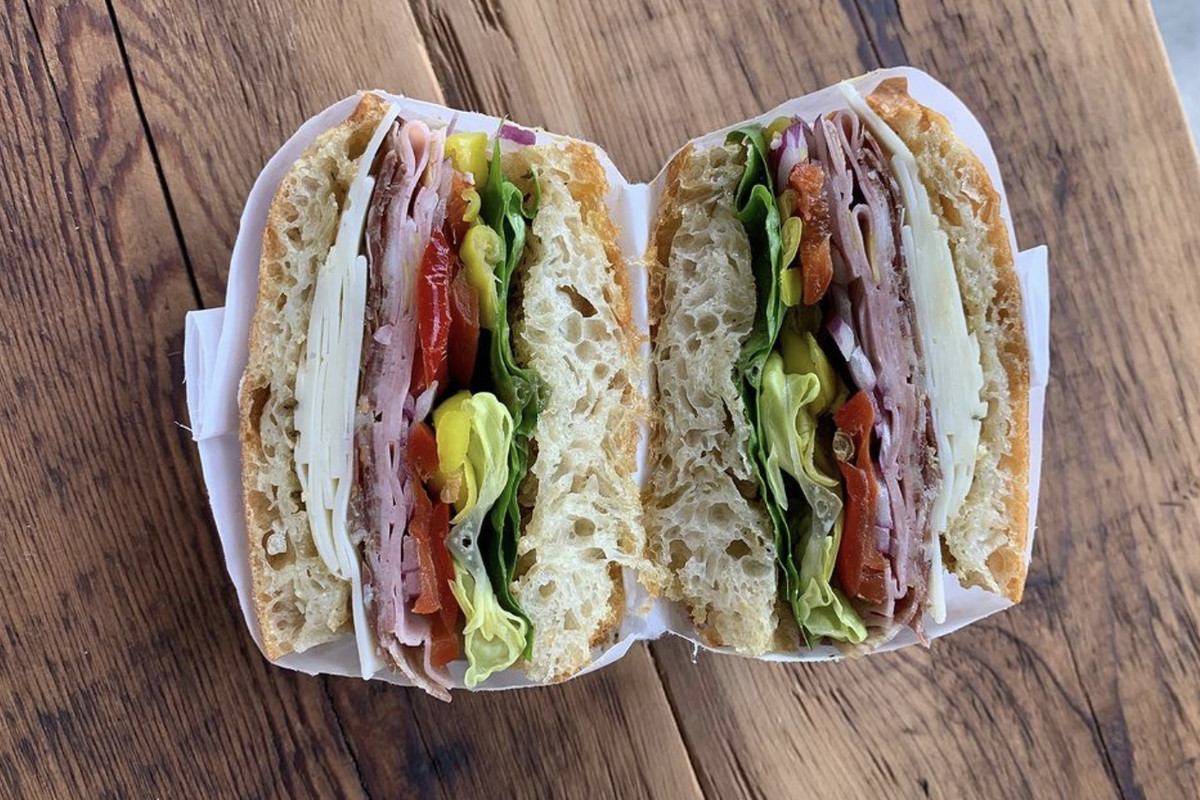 An overhead photograph of two halves of a sandwich, stacked with thinly sliced meats, cheeses, and vegetables on bubbly focaccia