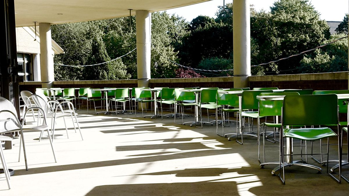 outdoor deck with green plastic restaurant chairs and tables