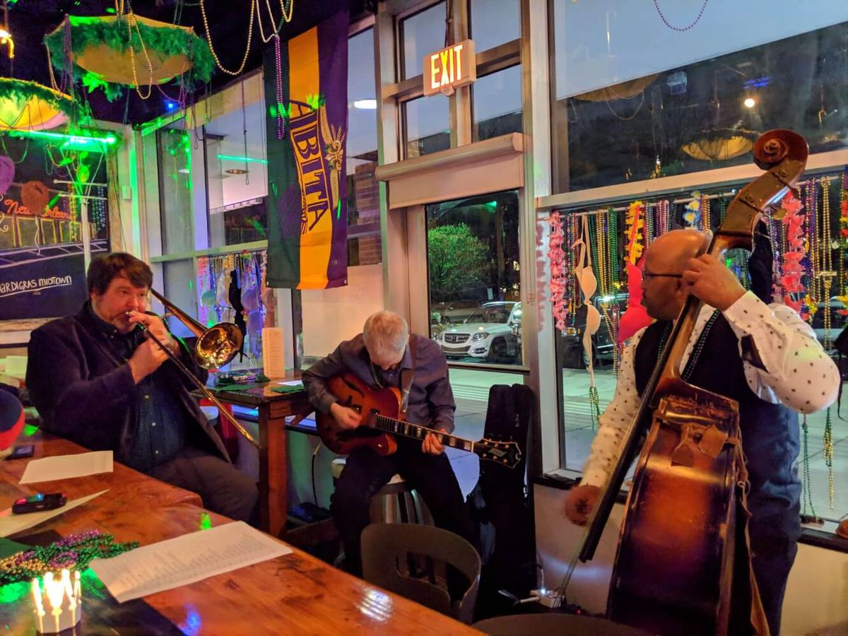Three male musicians playing the trombone, guitar, and bass for Mardi Gras pop up at Tapa Tapa in Midtown ATlanta