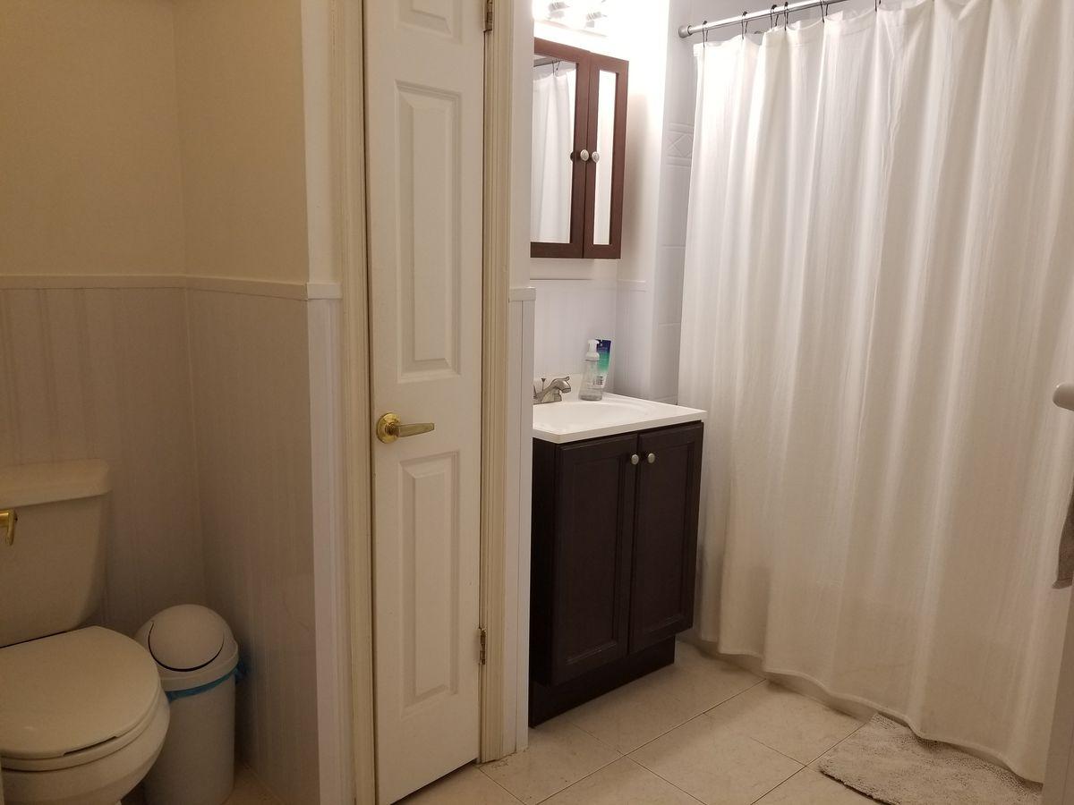 A bathroom with beige floor tiles.