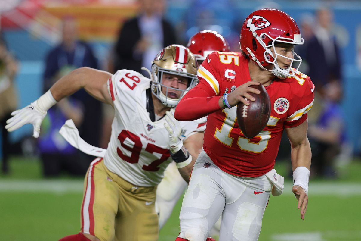 a football player wearing the red-and-white Kansas City Chiefs jersey (#15) scrambles with the ball while being chased by San Francisco 49ers #97