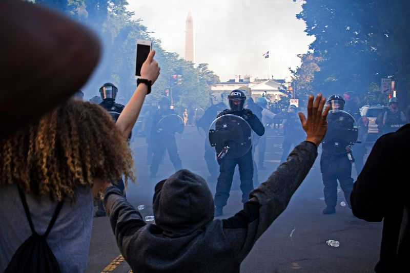 With the Washington Monument and White House visible in a haze of gas, security forces in riot gear stand in front of a group of protesters of color, all of whom have their arms raised.