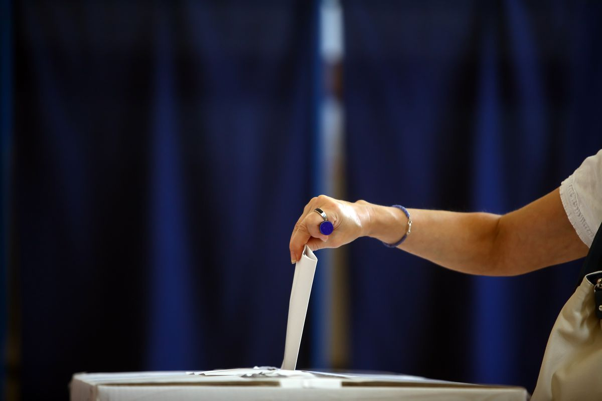 Woman drops a ballot in a ballot box