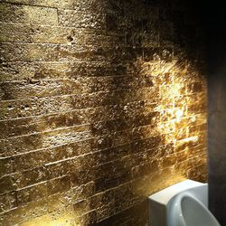 Gold wall above the urinal.