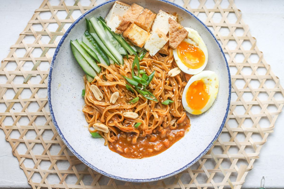A saucy brown noodle dish with a side of soft boiled eggs