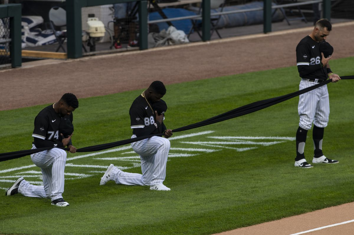 Chicago White Sox outfielderEloy Jiménez, left, and outfielderLuis Robert, center, kneel, while outfielderNicky Delmonico, right, stands during the National Anthem at the opening day game at Guaranteed Rate Field, Friday evening, July 24, 2020.