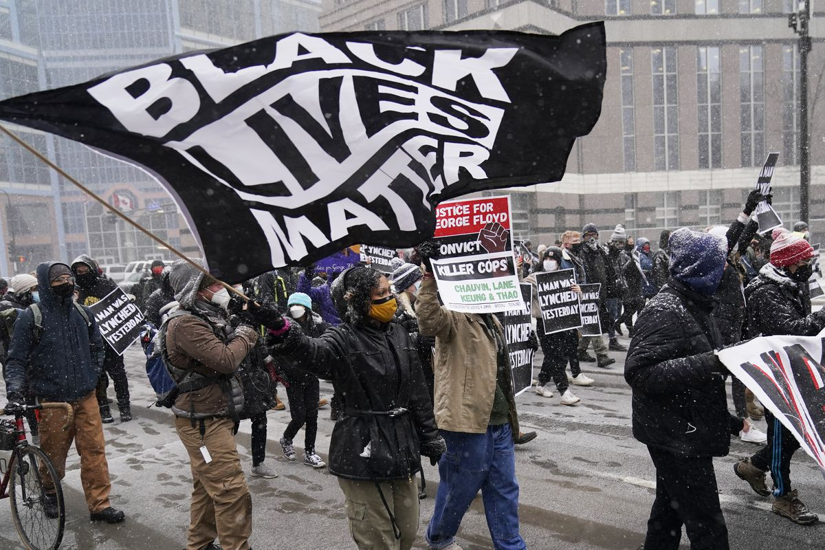 A group of protesters march in the snow around the Hennepin County Government Center, Monday, March 15, 2021, in Minneapolis where the second week of jury selection continues in the trial for former Minneapolis police officer Derek Chauvin. Chauvin is charged with murder in the death of George Floyd during an arrest last may in Minneapolis.