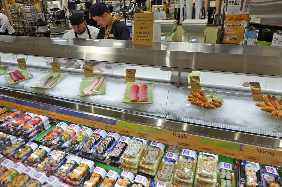 A sushi counter has a reach in refrigerator filled with sushi assortments.