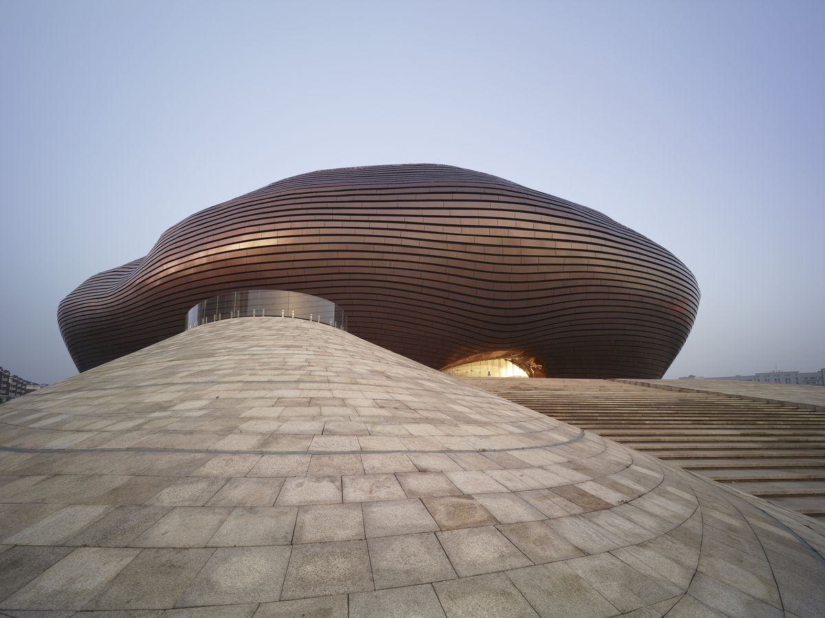 The facade of the Ordos Museum in China. The facade consists of metal tiles. The building structure is circular.