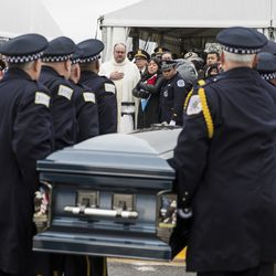 Officer Jimenez's wife, Crystal Garcia, watches as his casket is placed in the hearse. | Ashlee Rezin/Sun-Times