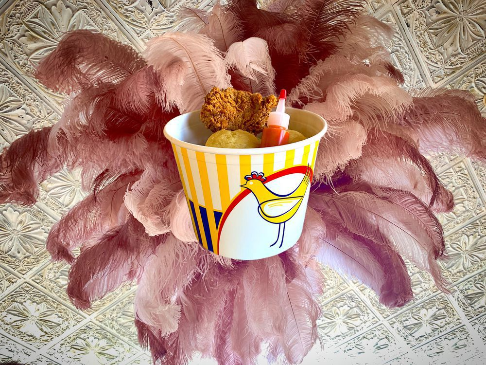 A bucket of fried chicken surrounded by purple feathers
