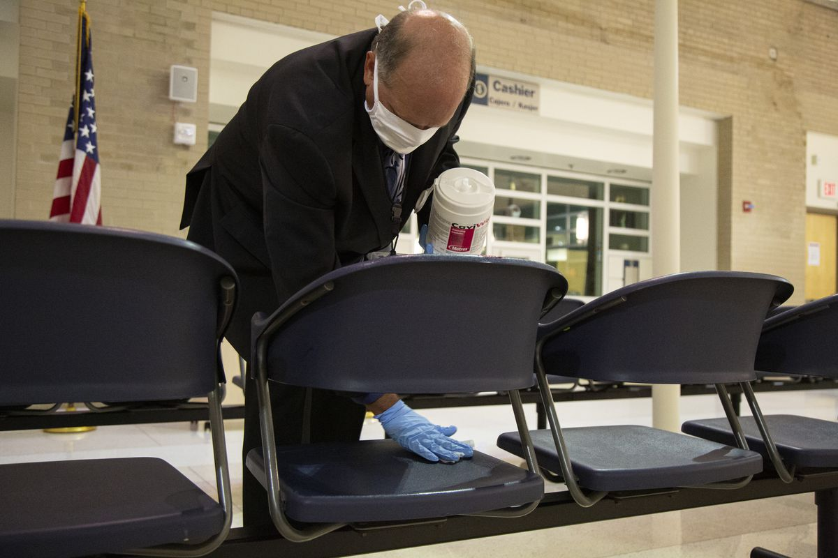Paul Phillips, branch chief of customer service for U.S. Citizenship and Immigration Services, disinfects seats before a naturalization ceremony in the South Loop.