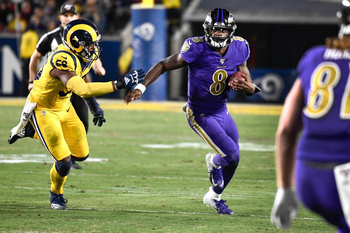 Baltimore Ravens quarterback Lamar Jackson tries to run past Los Angeles Rams defensive end Dante Fowler during the third quarter at Los Angeles Memorial Coliseum.