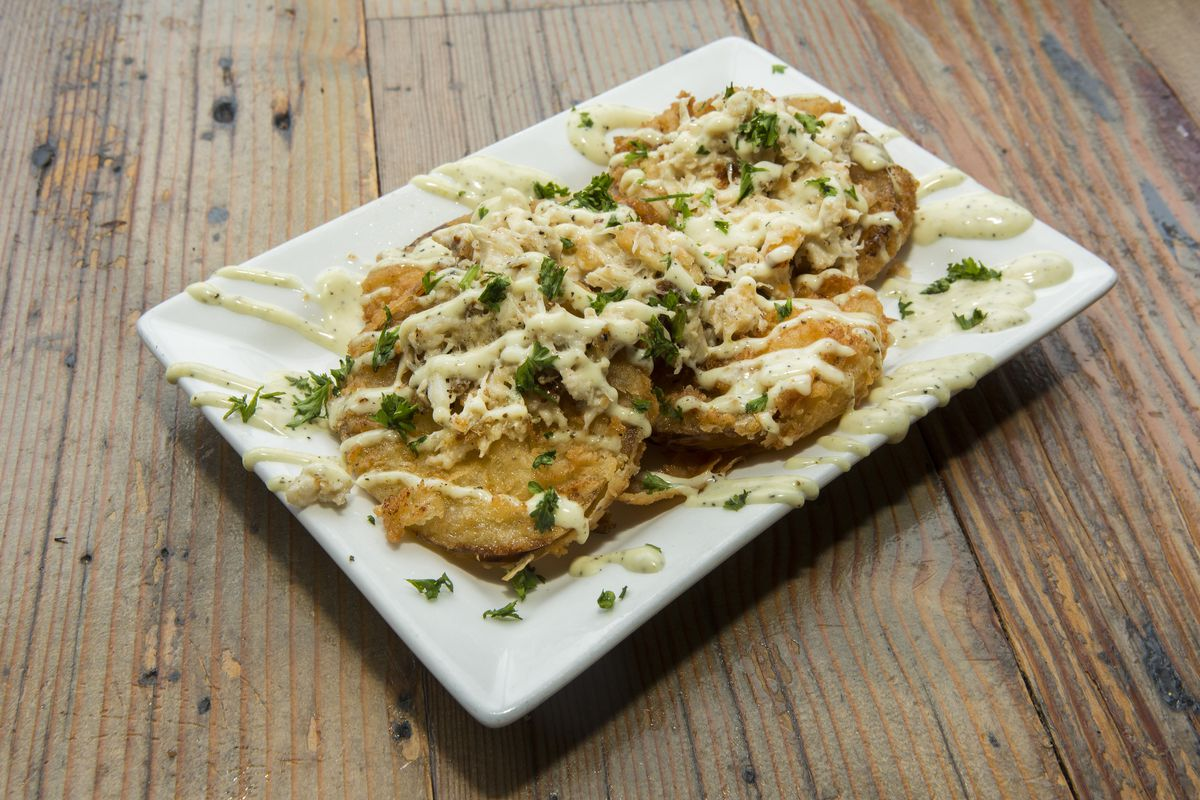 Three fried green tomatoes drizzled with white sauce and green herbs.