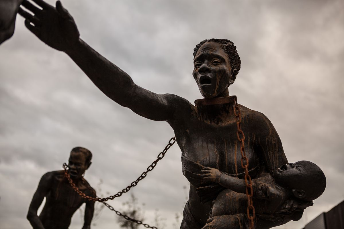 A set of statues at the National Memorial for Peace and Justice shows enslaved people bound by chains.