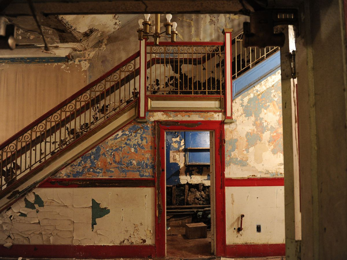 The shabby interior of an old theater, with peeling paint on the wall and a spindly staircase prominent in the picture.