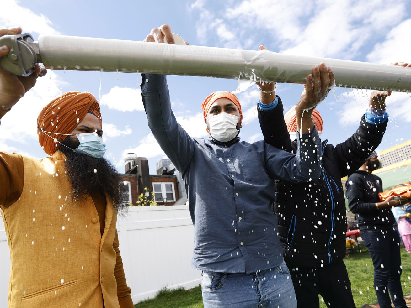 Jasbir Singh, left, and Vijay Singh wash a flagpole with milk as part of a ceremonial changing of the Sikh flag during Vaisakhi celebrations at Guru Nanak Darbar of Long Island, Tuesday, April 13, 2021 in Hicksville, N.Y.
