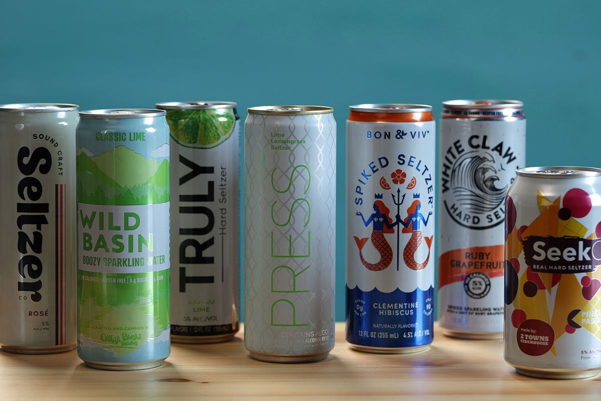 A row of cans of hard seltzer placed on a wooden countertop