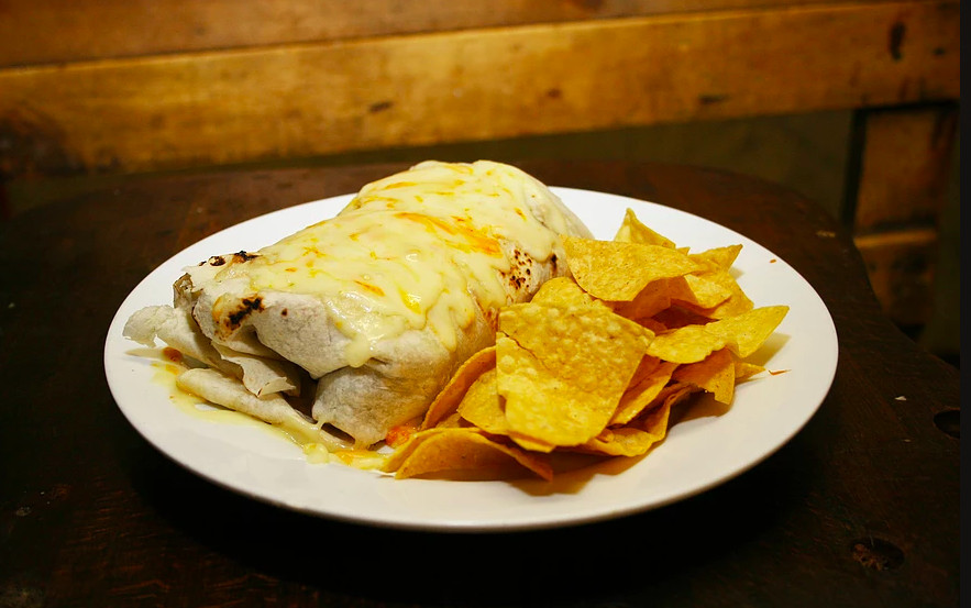 A burrito sits on a white plate with a side of tortilla chips. There's a wooden wall in the background.