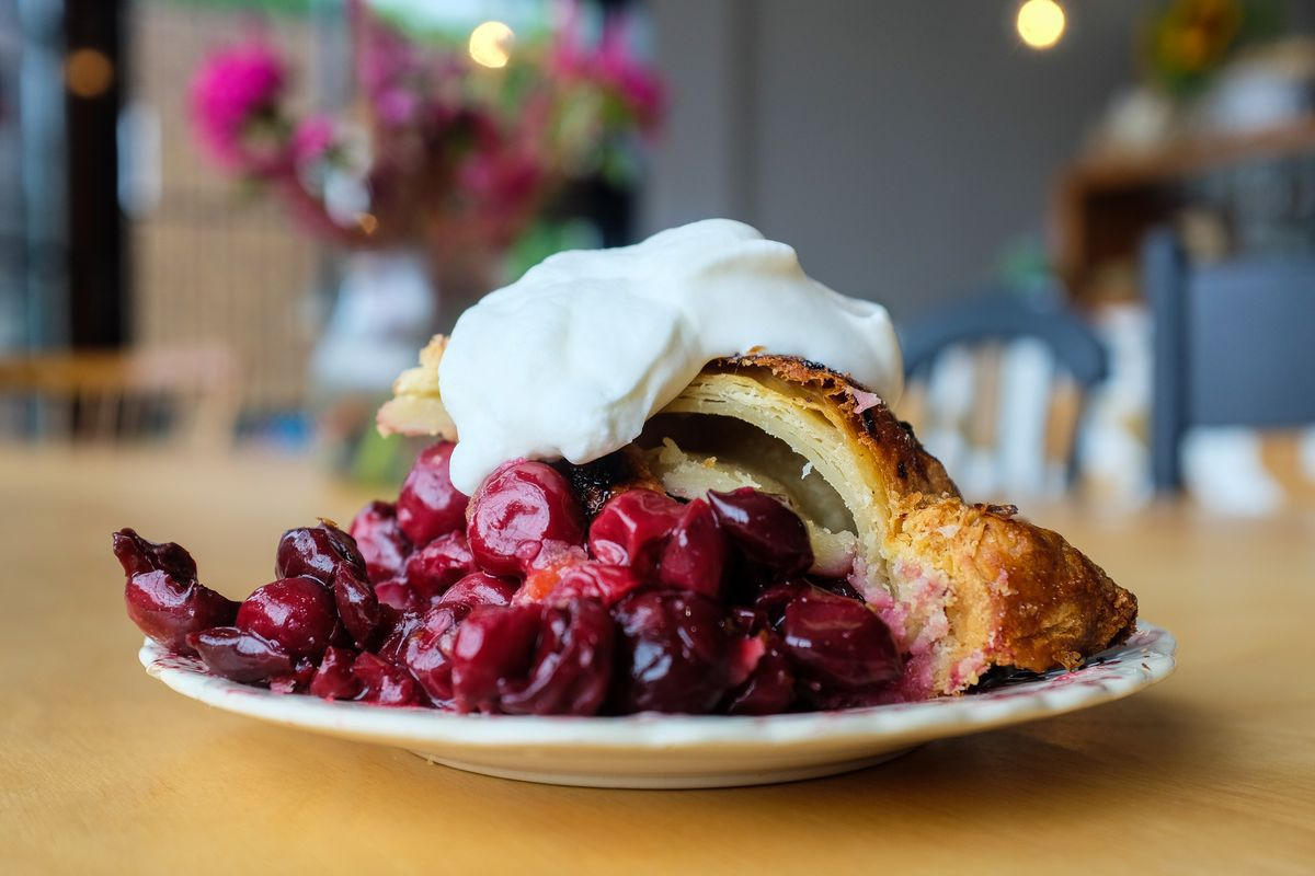A slice of pie collapsed on a plate with cherry filling falling out and a big dollop of fresh whipped cream on top.