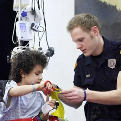 Alan Boykin,5, of Provo, does a craft with Salt Lake police officer Colton Lambert at Primary Children's Medical Center in Salt Lake City on Thursday, Jan. 19, 2012.  Boykin is recovering from surgery after having eaten magnets.