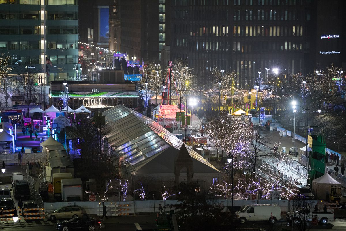 An aerial view of a winter festival with tents and glowing lights in the middle of tall buildings.