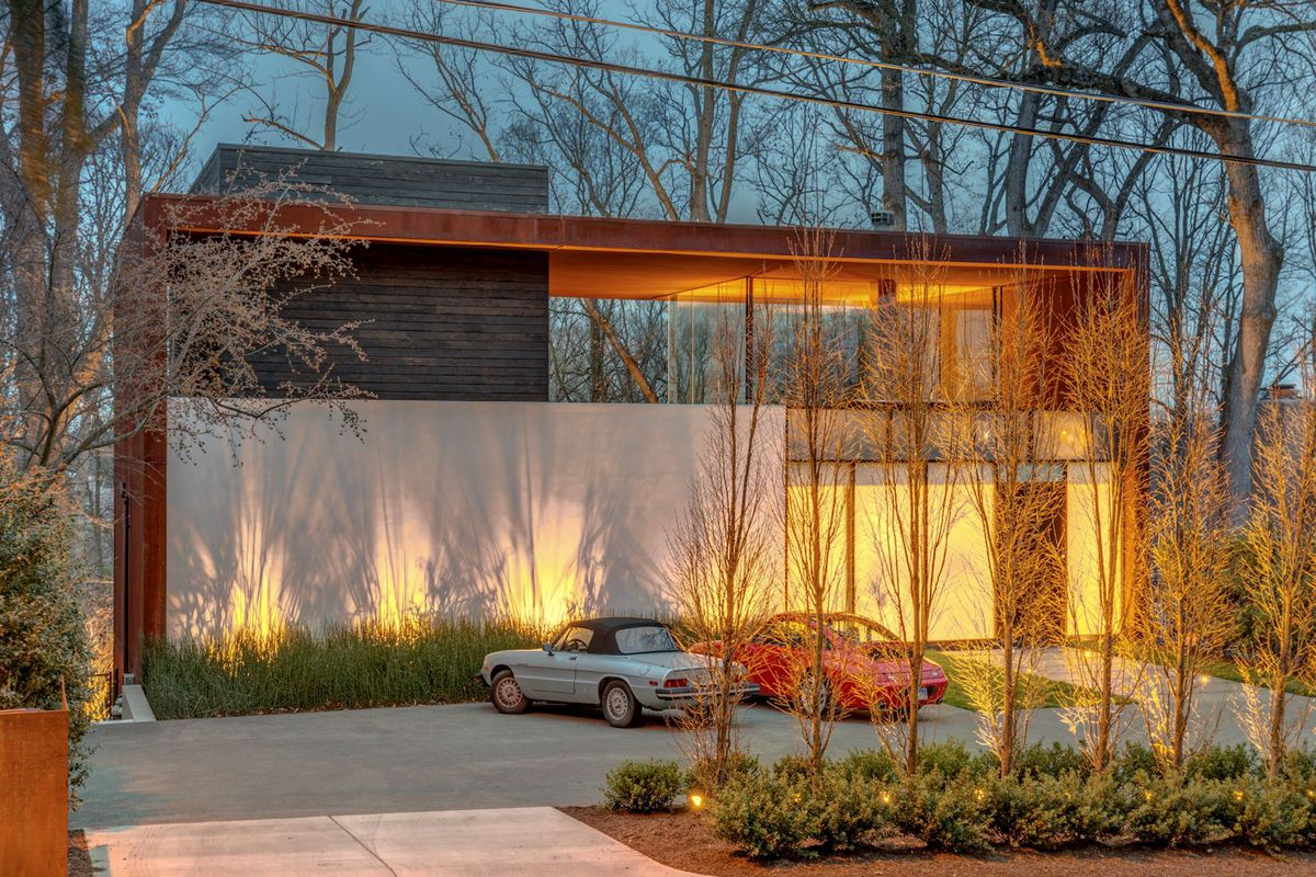 An exterior view of a boxy modern home at night.