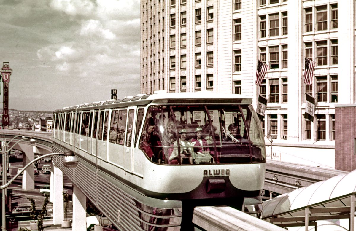 Passengers are visible in a muted film photo of the Seattle Monorail. The sign for the Orpheum Theater, which was turn down in 1967, is visible behind the monorail in this photo.
