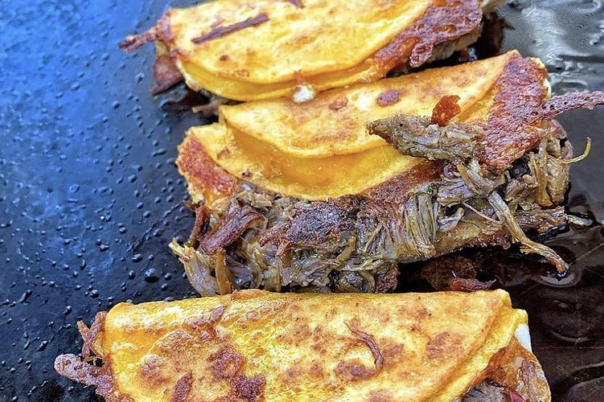 birria tacos on a griddle by Juana Tamale