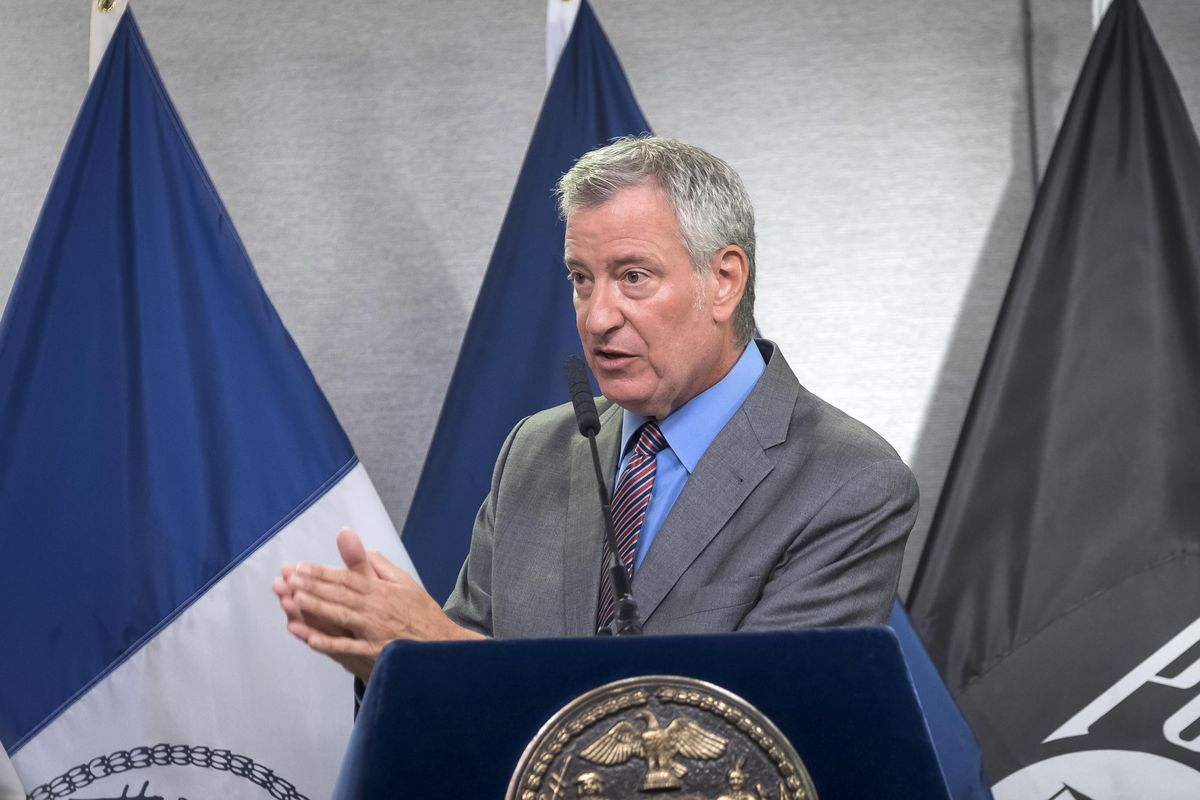Mayor Bill de Blasio stands at a lectern in front of three flags.