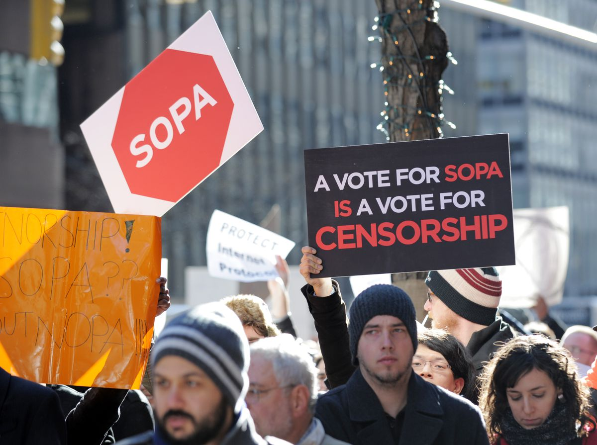 People hold signs at a protest by the te
