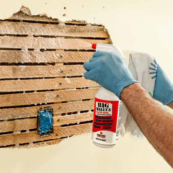 Person uses spray to wet plaster before repairing.