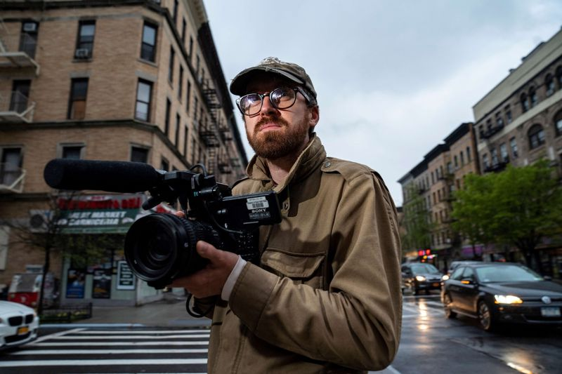 John Wilson holding his video camera while standing on a New York street.