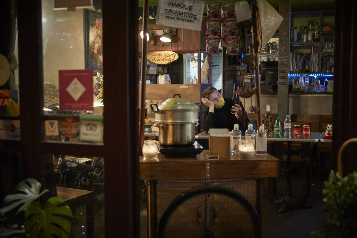A restaurant worker waits for customers in a closed restaurant offering take away food and drinks.