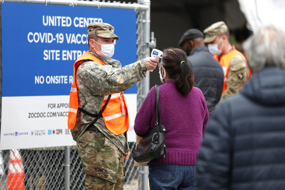 A National Guard member checks the temperature of people entering the United Center mass COVID-19 vaccination site on Wednesday, Mar. 10, 2021, in Chicago.