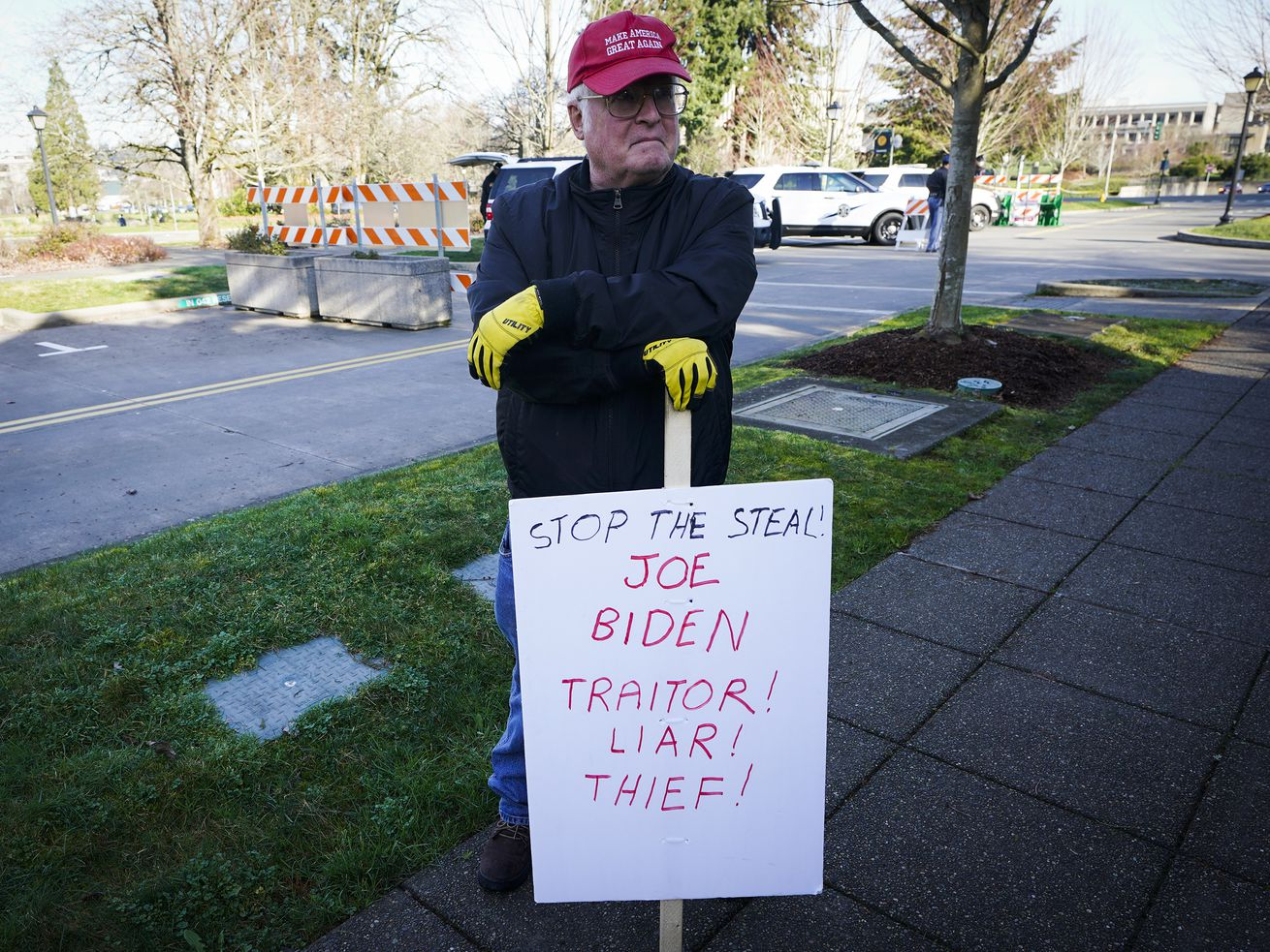 """A person wearing a MAGA hat stands on a sidewalk and leans on a sign that reads, """"Stop the steal. Joe Biden: Traitor! Liar! Thief!"""""""