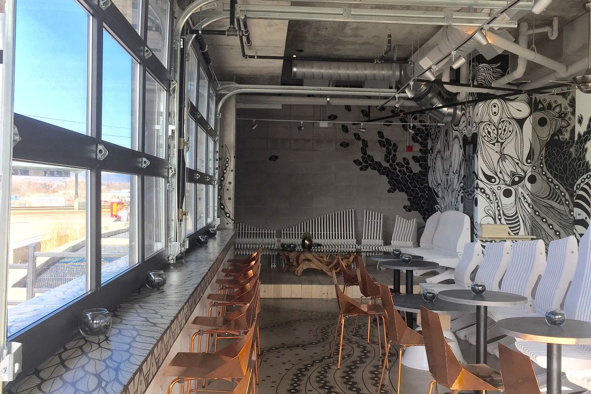 A photo of the interior of the shuttered White Whale Room with large garage doors on the left side, a counter with wood chairs and a large white mural visible