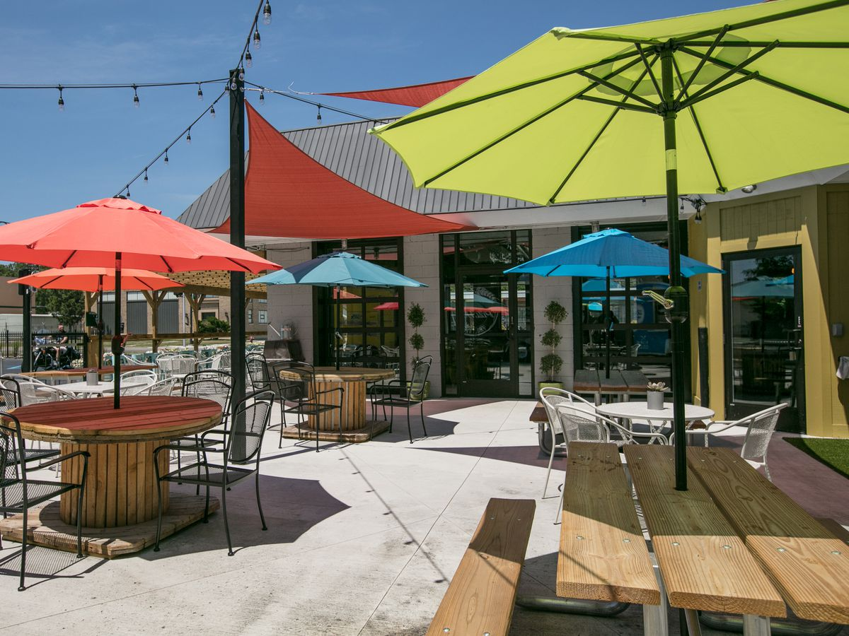 Colorful umbrellas over tables on the patio on a sunny day at Detroit Fleat.