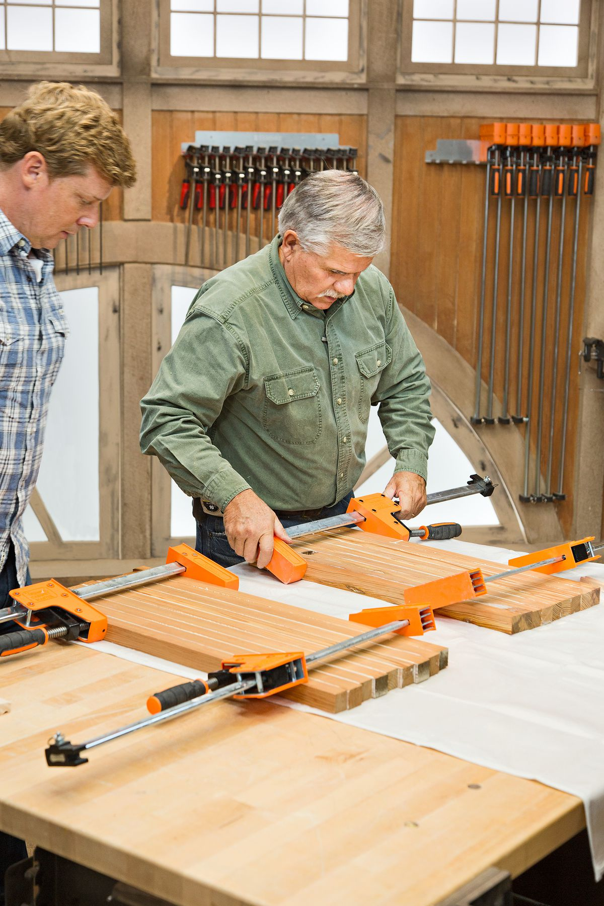 Person clamping the panels together to allow the glue to on the wood to dry.