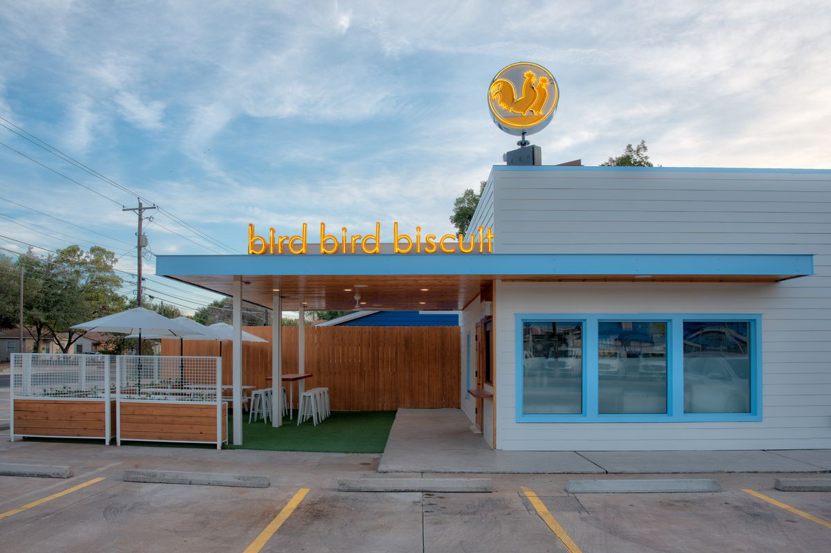"""A one-story restaurant with white walls and blue-trimmed awning and windows and a sign that reads """"bird bird biscuit"""" with a green patio with a white fence."""