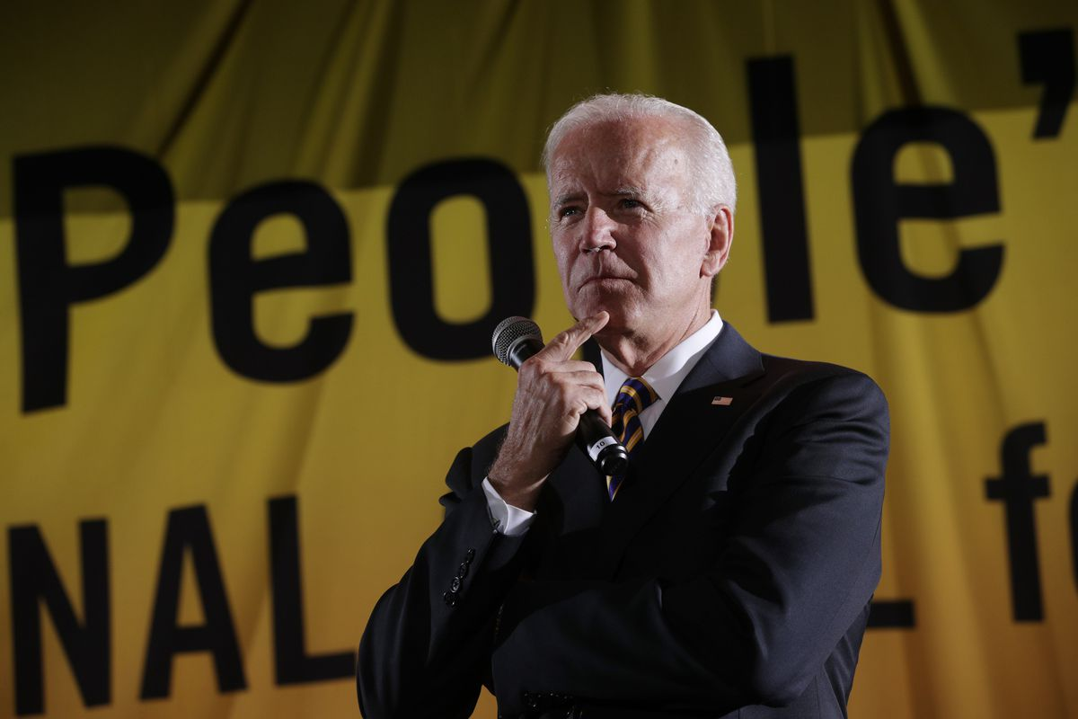 Democratic U.S. presidential hopeful and former Vice President Joe Biden is wearing a suit and holding a microphone as he stands in front of a bright yellow banner.