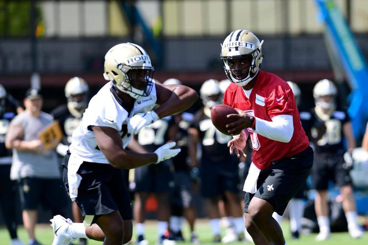 METAIRIE, LA - New Orleans Saints quarterback J.T. Barrett (5) rehearses a handoff to tryout running back Josh Rounds (24) during rookie minicamp practices at the Ochsner Sports Performance Center.